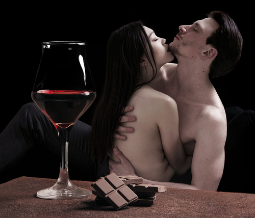 Red wine glass and chocolate with lovers portrait cuddling